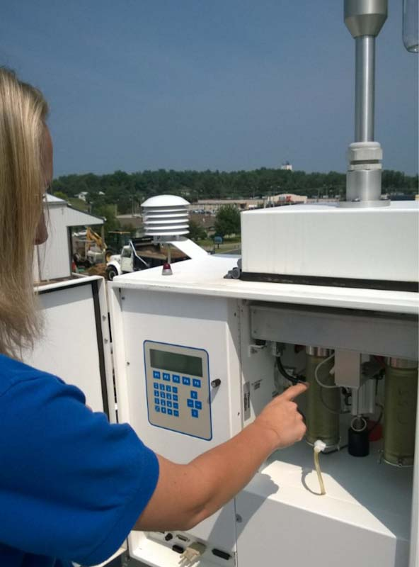 An air monitoring specialist works with a PM2.5 manual sampler.