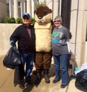 Mascot Ollie the Otter stands with two other people at an outreach event.